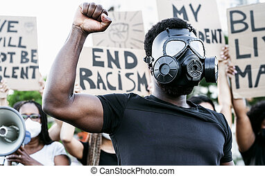 Activist wearing gas mask protesting against racism and ...