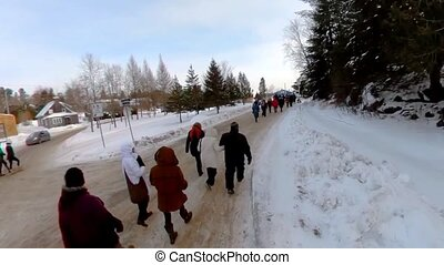 A high angle video of ecological activists marching along a snow-covered track, braving adverse weather conditions, united against environmental issues.