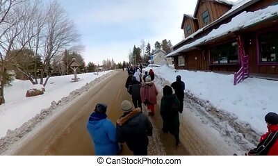 High angle footage on a group of ecological campaigners marching through a snowy town during winter. People wearing padded coats unite against global warming.