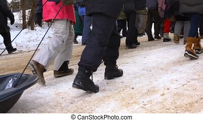Low angle footage on a group of protestors marching for planet earth. Legs of activists are seen marching past. A young child is pulled along the snow in a sled