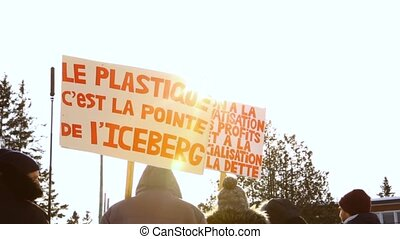 Low angle shot of protestors holding signs during an environmental rally. A French placard, saying the plastic is the tip of the iceberg, is seen as camera pans