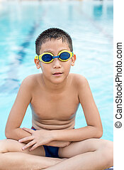 Activities on the pool, child sitting at swimming pool in  summertime