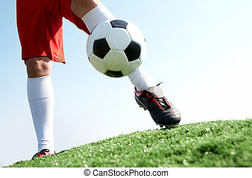 Activity - Horizontal image of soccer ball being kicked by...