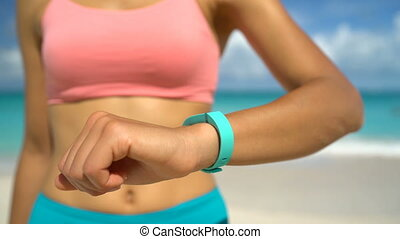 Activity tracker on fit young woman wrist standing with hand on hip at beach. Runner is wearing turquoise colored activity fitness tracker watch on sunny day. Female is in sportswear.