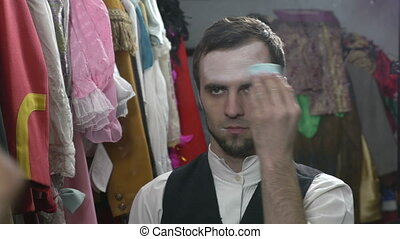 Actor applying makeup for mime fac - Handsome young male ...