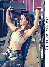 Actove young woman workout her arms in fitness club gym