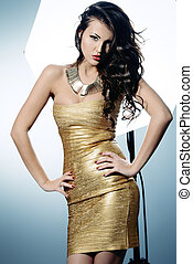 actress - Fashion shot of a gorgeous young woman in golden...