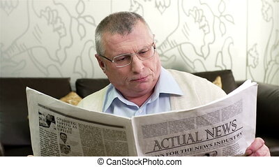 Actual News - Close-up of a handsome senior man reading a...
