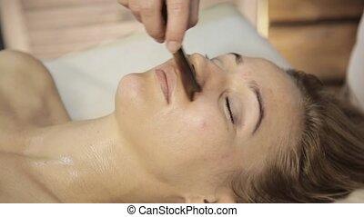 Acupressure on a female face. Chinese alternative massage...
