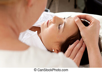 Acupuncture Facial - Over the shoulder shot of professional ...