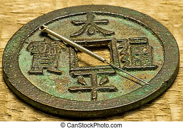 acupuncture needles on chinese coin