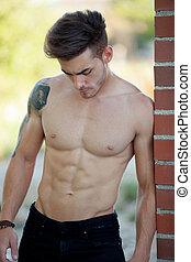 adattare, atletico, shirtless, giovane, contro, parete, sporgente, uomo mattone, bello