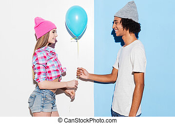 Add some colors. Handsome young African man giving a blue balloon to his girlfriend while standing against colorful background
