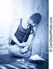 addict with syringes and  with drugs sitting on the floor