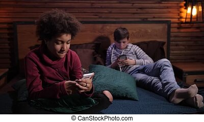 Close-up of busy on cellphones mixed race teenage friends during joint leisure in domestic room. Teenage schoolboys ignoring each other sitting on bed apart and surfing the net on smartphones