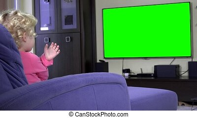 Addicted little girl point finger and wave looking tv. Green...