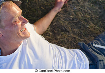 Addicted man laughing lying down on grass
