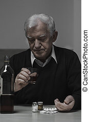 Addicted retiree drinking whiskey and taking drugs