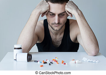 Addicted to these pills. Frustrated young man sitting at the...