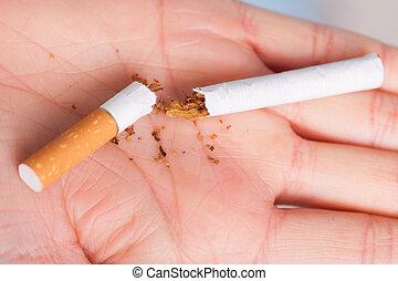 Addiction. Broken cigarette on hand. Quit smoking - ...