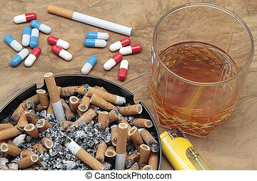 addiction - cigars on a ashtray full of ash, pills and...