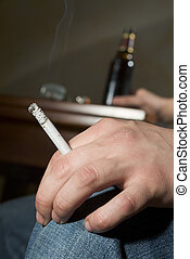 Addiction to smoking and alcohol - Man drinking from a...