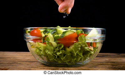 adding a salt to salad in glass bowl
