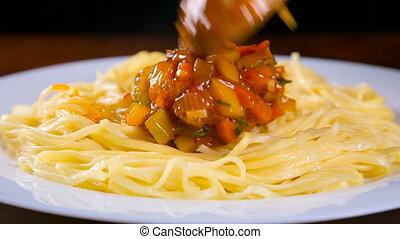 adding a vegetable sauce to pasta, closeup