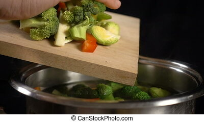 Adding a vegetables to boiling soup in pan, slow motion