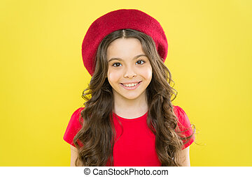 Adding an edge to the classic French look. Small child smiling with fashion look. Happy little girl wearing red beret for the ultimate cool girl look. Trendy look