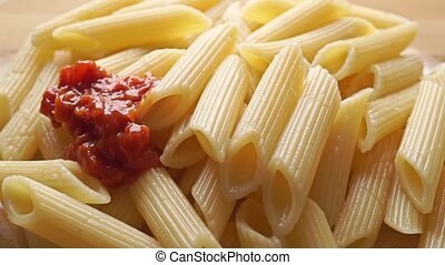 Adding dense red vegetable sauce to freshly cooked pasta penne