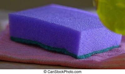 Adding detergent on violet sponge - Adding dish washing...