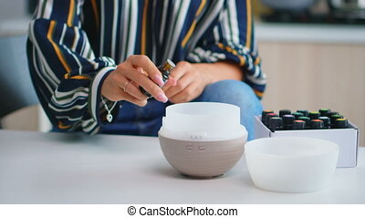 Close up of woman adding essential oils into diffuser. Aroma health essence, welness aromatherapy home spa fragrance tranquil theraphy, therapeutic steam, mental health treatment