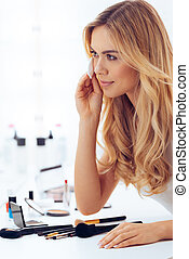 Adding final touches. Side view of beautiful young woman using cotton disk and looking at her reflection in mirror while sitting at the dressing table