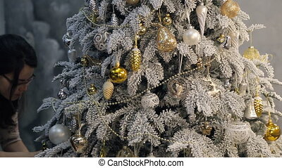 adding finishing touches to decoration of Christmas tree.