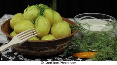 Adding fresh dill to boiled new delicious potato on plate on...