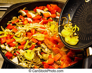 Adding fried onion to pan vegetables.