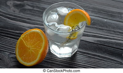 Adding ice cubes in glass with fresh cocktail - Adding ice...