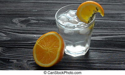 Adding ice cubes in glass with fresh cocktail