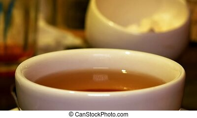 Adding lump sugar with pincers to black tea in cup - Adding...