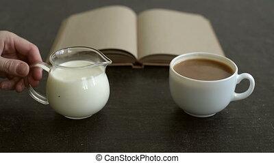Adding milk to coffee - Female hand adding milk to coffee.