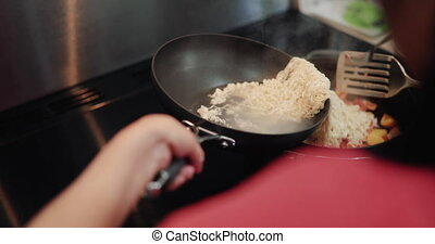 Adding Noodles to a Stir Fry - Adding cooked noodles to...