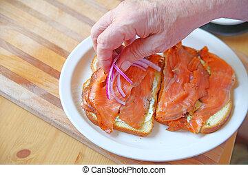 Adding onions to smoked salmon sandwich - A man puts sliced...