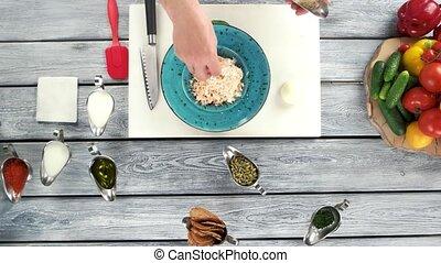 Adding parmesan cheese to pasta.