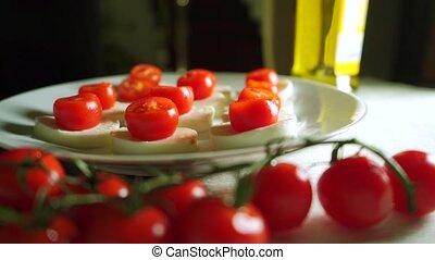 Adding pesto sauce to mozzarella and tomato salad Caprese ....