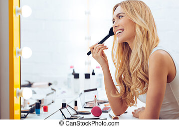 Adding some color to my cheeks. Side view of cheerful young womanapplying make-up and looking at her reflection in mirror while sitting at the dressing table