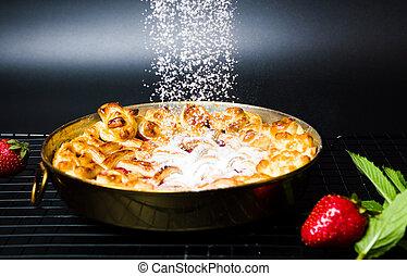 Adding sugar on strawberry sweet pie