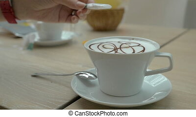 Adding sugar to the coffee served in cafe