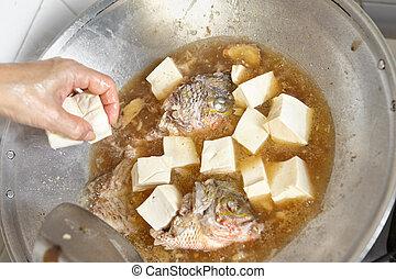Adding tofu to the fish stew on the wok