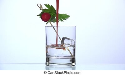 Adding tomato juice over vodka - closeup with white...